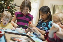 A group of children, girls and boys, around a table, decorating organic chris Stock Photos