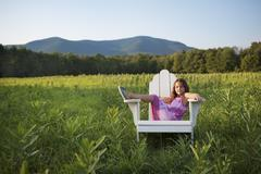 A young girl sitting in a traditional wooden adirondack style chair in a fiel Stock Photos