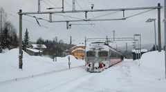 Commuter train leaving station in snow weather Stock Footage
