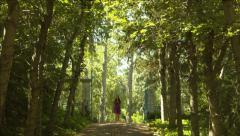 Beautiful Teen Girl In A Lavender Dress Approaching On Idyllic Sun-Dappled Lane Stock Footage