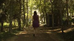 Beautiful teen girl walks down tree-lined lane toward manor Stock Footage