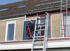 man climbing the ladder with solar panel - stock photo
