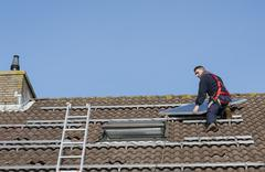 man putting the solar panel on the roof - stock photo