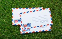 letters air mail on green grass - stock photo