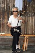 an old man plays the erhu, anhui, china - stock photo