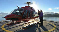 Low angle of crew loading passengers into a helicopter and taking off from a Stock Footage