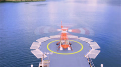 Oblique angle of a helicopter lifting off from a ship helipad near Bahia Tictoc - stock footage