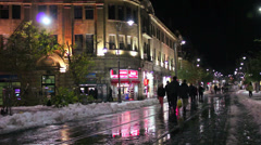 People walk through unusually snowy streets in Jerusalem at night. Stock Footage