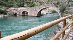 River flows under the old stone bridge - stock footage