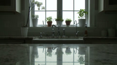Potted plants adorn a window and are reflected in the countertop in a kitchen. - stock footage