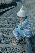 small girl seating on railroad tracks, india - stock photo