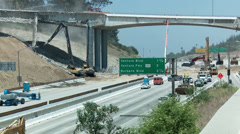 View of heavy equipment tearing down part of a bridge over the 405 freeway in Stock Footage