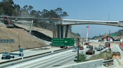 Wide view of heavy equipment tearing down part of a bridge over the 405 freeway Stock Footage