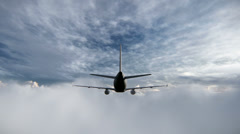 Plane flying between clouds Stock Footage