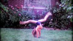 818 - young girl does gymnastic routine in backyard - vintage film home movie Stock Footage