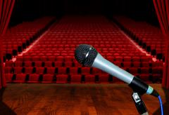 Microphone on stage facing empty auditorium seats Stock Photos