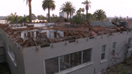 Stock Video Footage of Wide shots of the exterior walls of a house in the process of being demolished.