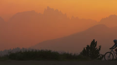A mountain biker pulls to a stop on a hillside at sunset and takes a picture. Stock Footage