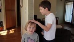 Stock Video Footage of Brother Measuring Little Sister's Height