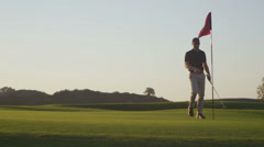 A golfer removes a flag from a hole on a golf course. Stock Footage