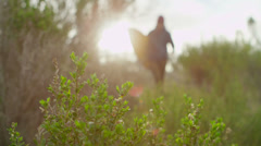 A surfer carries his board as he hikes down to a remote surf spot in a coastal Stock Footage