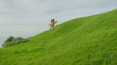 A surfer carries his board up a hill as he hikes to a remote surf spot in a - stock footage