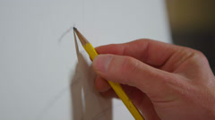 Close-up of a hand as an artist begins to sketch on a blank canvas. Stock Footage