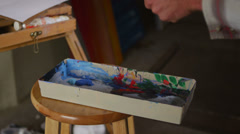 Close-up of an artist mixing colors on a palate. - stock footage