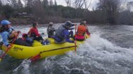 Stock Video Footage of Rafters paddle through rapids on a river.