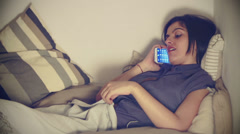 Brunette woman use smartphone in bed in bedroom at home Stock Footage
