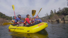 Rafters hold their oars aloft as they travel down a river. . - stock footage
