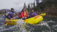 Stock Video Footage of Rafters paddle down a fast flowing river.