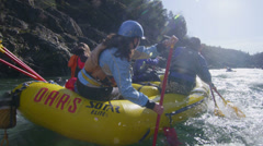 Rafters paddle and negotiate rapids on a fast flowing river. - stock footage