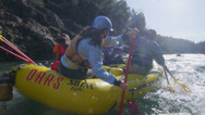 Stock Video Footage of Rafters paddle and negotiate rapids on a fast flowing river.