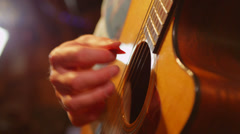 Close-up of a hand strumming a guitar. - stock footage