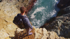 High angle view of a man looking down at the ocean from the edge of a sea cliff. Stock Footage
