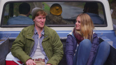A couple sits in the back of a pickup truck as it pulls away. Stock Footage