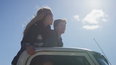 A couple stands in the bed of a pickup truck as it drives along a rural road. - stock footage
