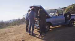 A group of friends stand around an old blue pickup truck with its hood up on the Stock Footage