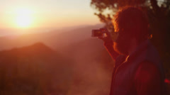 A man takes a picture of the sunset at a campsite. - stock footage