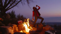 A man sprays lighter fluid on a campfire while drinking beer at a campsite. Stock Footage
