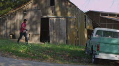 A man carries a board to a pickup truck parked outside an old barn. Stock Footage