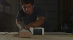 A woodworker saws a plank on a workbench. - stock footage