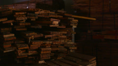 Pan right across wood planks stacked in a workshop. Stock Footage