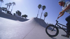 The camera follows a BMX bike rider as he jumps and rides the wall of a - stock footage