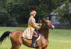 history fan dressed as 17th century polish cavalryman with a sabre in his han - stock photo