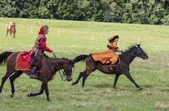 history fans dressed as 17th century polish gentry ride on horseback - stock photo