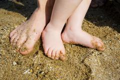 feet of child and adult on the sea sand - stock photo