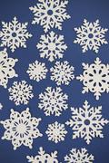 Paper Cut Out Snowflake Background - stock photo