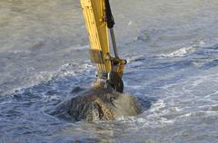 Stock Photo of dredging harbor with excavator